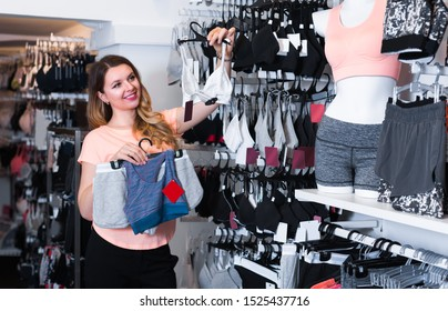 Female is choosing sports underwear in lingerie shop.