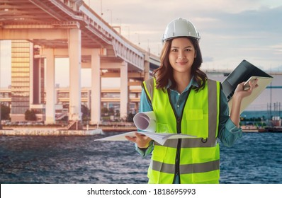 Female Civil engineer with computer and blueprint is standing infront City tranportation bridge over river for city development.