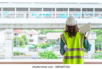 Female Civil engineer is working on tranportation development in the background.