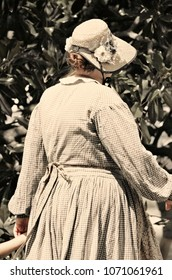 A female Civil War re-en actor in period dress participates in a recreation of a battle and camp.