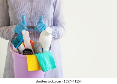 Female cleaner holding a bucket with cleaning supplies. Cleaning concept.