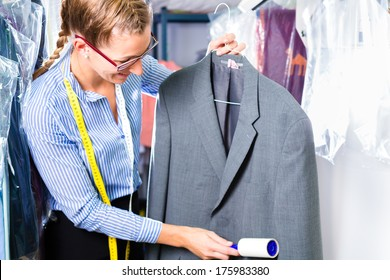 Female cleaner in laundry shop checking clean clothes removing lint with roller