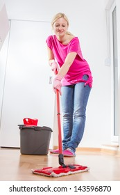 Female cleaning and mopping floor at home.