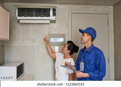 Female client asking service worker to fix air conditioner