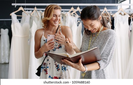 Female client in bridal boutique with tailor holding a diary. Wedding designer with woman customer in wedding fashion store.
