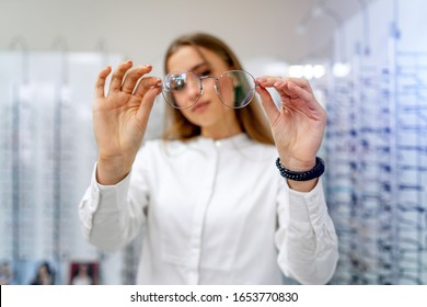 Female client or optician is standing with raw of glasses in background in optical shop. Stand with spectacles. Eyesight correction. Girl in glasses is posing to the camera. - Shutterstock ID 1653770830