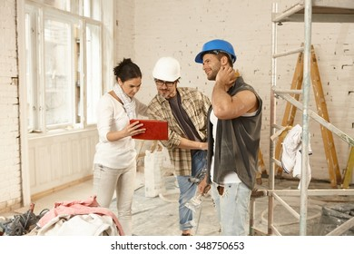 Female client showing plans on tablet computer to contractors, standing at renovation site.