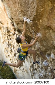Female climber ascending an overhanging rock face in Joshua Tree National Park.