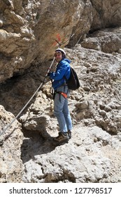 female climber ascending rocks on equipped pathway, Italian Dolomites