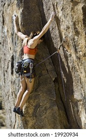 Female climber ascending a steep rock face in Joshua Tree National Park on a sunny day.