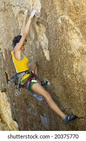 Female climber ascending a steep rock face in Joshua Tree National Park.
