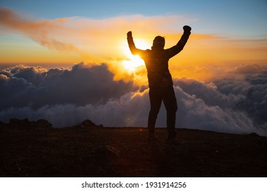 Female climber celebrating on top of Acatenango volcano in Guatemala watching the sunset - happy woman with hands up hiking enjoying the sunset