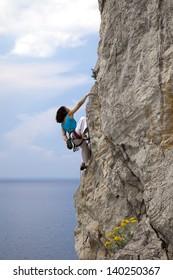 Female climber climbs the natural rock.