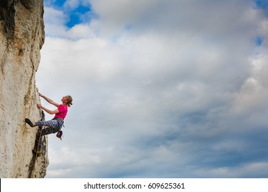 Female climber hanging by a cliff