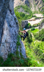 """Female climber hanging from a via ferrata cable on """"Astragalus"""" route, a popular tourist attraction in Bicaz Gorge (Cheile Bicazului), Neamt county, Romania. Aerial view from high above on a mountain."""