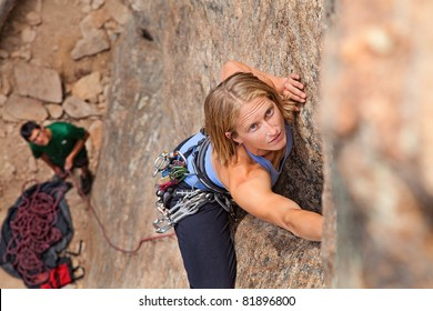 Female climber and her partner rock climbing