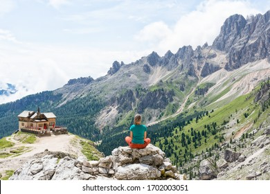 Female climber meditating and looking over the valley close to Rifugio Vajolet, Dolomites, Italy on a sunny day