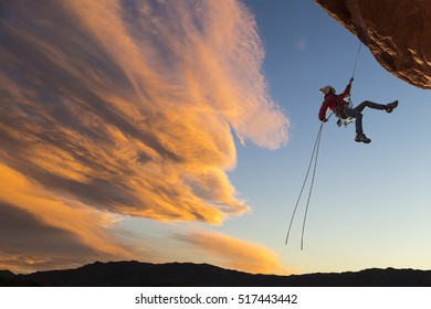 Female climber rappelling down a sheer cliff.