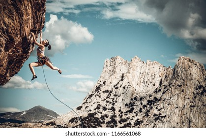 Female climber struggeling up a sheer cliff.