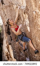 Female climber struggling up a sheer cliff.