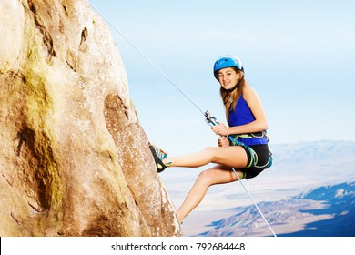 Female climber using abseil method of roping down