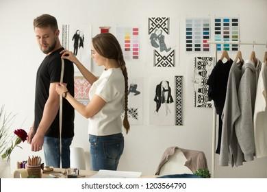 Female clothes designer, dressmaker taking man, customer, model measurements with measure tape in workshop, fashion design studio, preparing for sewing, dressmaking handmade unique personal order