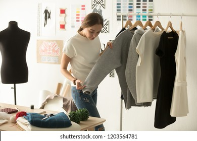 Female clothes designer working with new woman wear collection in cozy workshop studio, fashion designer, dressmaker standing near clothes rack, touching, holding in hands fashionable handmade clothes