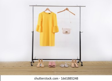 female clothing with yellow sundress with  handbag on hanger with four high hell shoes on wooden background