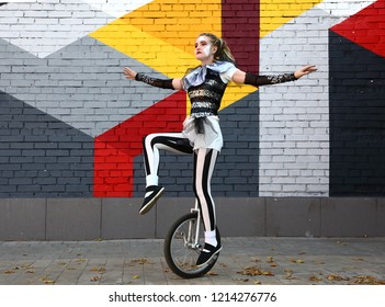 Female clown in circus clothes rides a unicycle outdoors