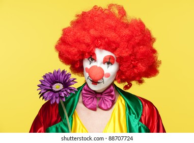 a female clown with colorful clothes and makeup holding a flower