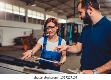 Female CNC machine operator checking program code on computer with supervisor in industrial factory hall