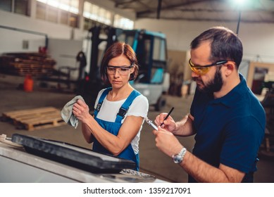 Female CNC machine operator and factory supervisor working at computer in the industrial hall