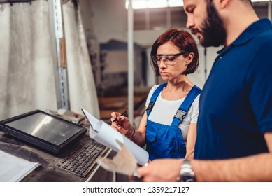 Female CNC Machine Operator and industrial engineer checking product drawing in industrial factory hall