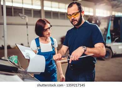 Female CNC Machine Operator and industrial engineer measuring cut out product with a caliper