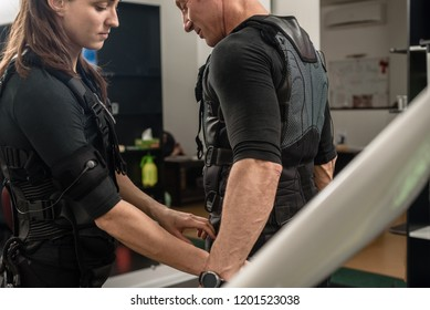 Female coach helping man with putting electro muscular stimulation suit on