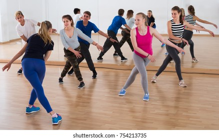 Female coach holds group dance training in studio