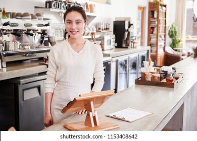 Female coffee shop owner standing behind counter smiling