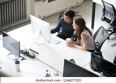 Female colleague discuss project together at workplace, talking, chatting in office during coffee break, employees brainstorming, reading funny good news, looking at screen, working together top view