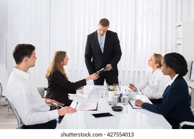 Female Colleague Showing Document To Young Businessman In Meeting