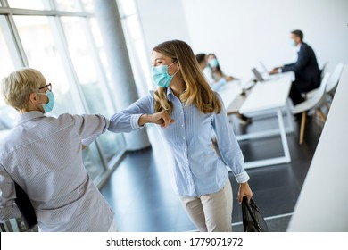 Female colleagues keeping social distance in the office, greeting each other by bumping elbows, preventing covid 19 coronavirus infection spread