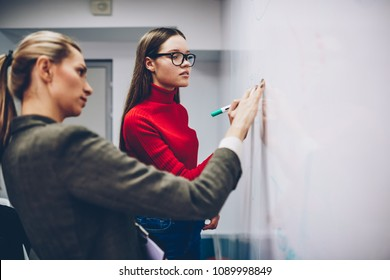 Female colleagues standing near flip chart for discussing strategy and ideas on brainstorming session, skilled woman coach explaining information for young girl student on lesson writing on board
