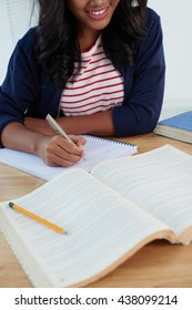 Female college student with book writing to notebook at college