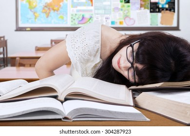 Female college student with long hair, studying in the classroom and take a rest on the table