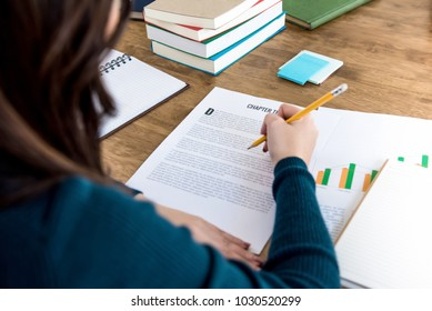 Female college student reading information on paper doing homework assignment at the table