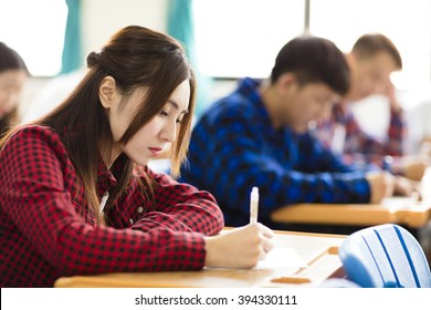 female college student sitting and exam in the classroom