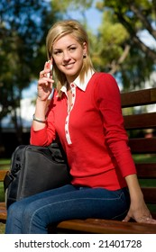 A female college student sitting on a bench with laptop bag and mobile phone