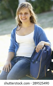 Female College Student Sitting On Bench With Book