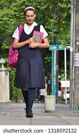 Female College Student Wearing Uniform Walking On Sidewalk