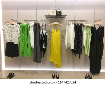 female colorful clothing ,shoes ,handbag set of on the racks in clothing store