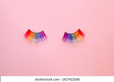 female colorful rainbow LGBT eyelashes isolated on pink background, copy space, top view